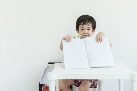 Closeup asain kid show a note book after school on white cement wall background Stock fotó