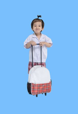 Closeup a little kid in student uniform with schoolbag isolated on blue background