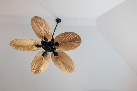 Closeup ceiling fan on white cement house ceiling background