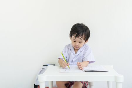 Closeup asain kid sitting to do homework after school on white wall background