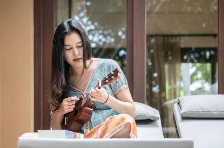 Closeup asian woman playing ukulele on sofa at the terrace