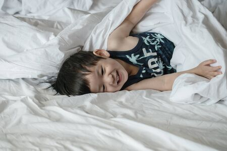 Closeup asian kid on bed with fun motion in the morning