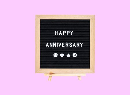 Closeup a board with happy anniversary word isolated on pink background