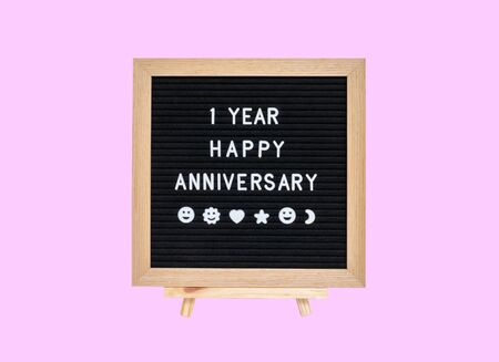 Closeup a board with 1 year happy anniversary word isolated on pink background