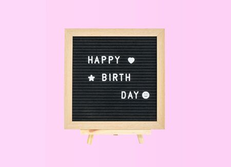 Closeup a board with happy birth day word isolated on pink background