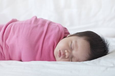Closeup a baby sleeping comfortably on the bed