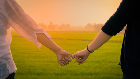 Close up Two Asian women wearing white and black shirts stand   be hand in hand  and look at the green Field morning light.