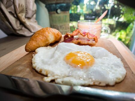 bacon and eggs: Breakfast with croissants, bacon, eggs Claire hot coffee on a wooden tray. Stock Photo