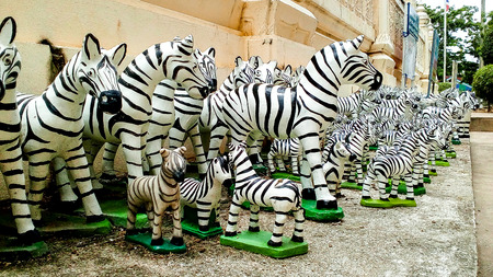 Zebras are placed in front of the spirit house. Zebra stucco votive offering to guardian spirit away. Stock Photo