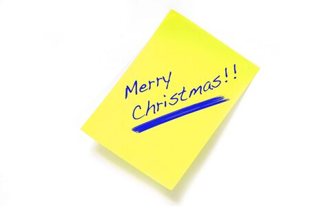 Merry Christmas written on a yellow post it on a white background photo