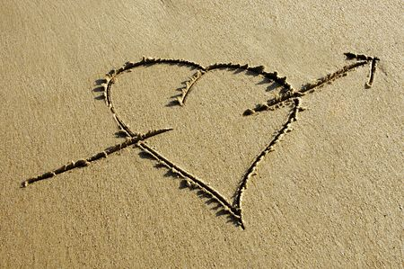 evoking: heart  with arrow drawing  in the sand