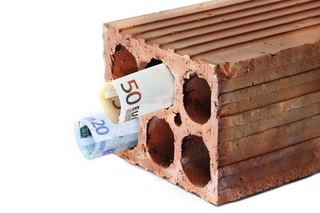 subprime mortgage crisis: money within a brick symbolizing the mortgage crisis