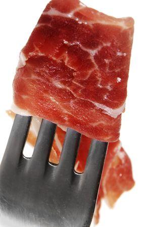 a closeup of a serrano ham with a fork