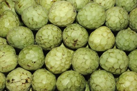 annona: a pile of cherimoyas in a vegetables market