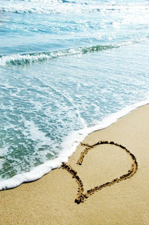 hearts drawn on the sand of the beach photo