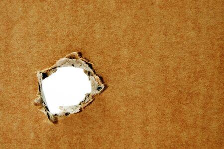 carton: een gat in een bruine kartonnen achtergrond  Stockfoto