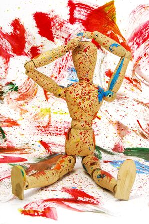 wooden puppet splashed with paint of different colors on a different colors background photo
