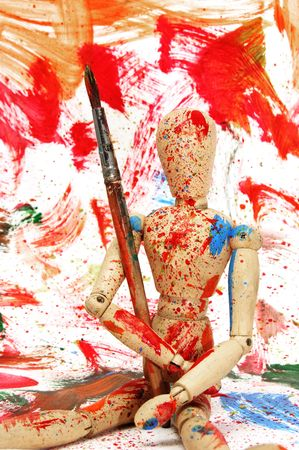 wooden puppet splashed with paint of different colors photo