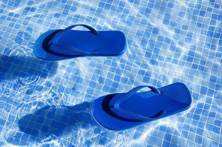 swimming shoes: a pair of flip-flops floating on the water on a swimming pool