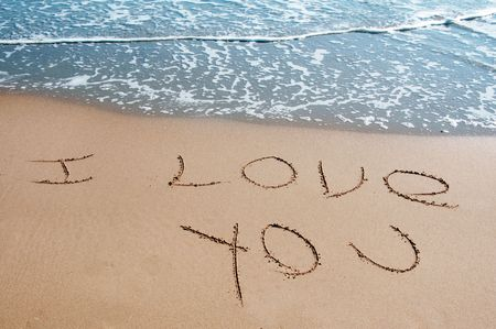 declaration of love: i love you written on the sand of a beach