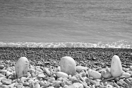 a pile of pebbles in the sea shor in black and white photo