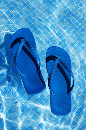 a pair of flip-flops floating on the water on a swimming pool photo
