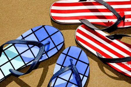 sandalias: dos pares de Flip-Flops flotando en la arena en una playa