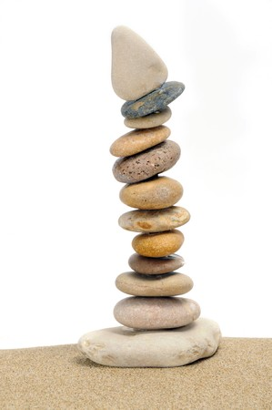 a pile of zen stones and sand on a white background photo