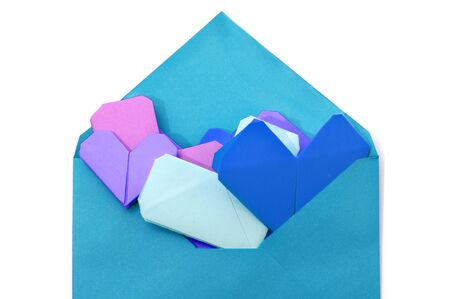 paper hearts of different colors inside an envelope on a white background photo
