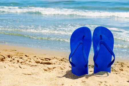 a pair of flip-flops stuck on the sand of a beach photo