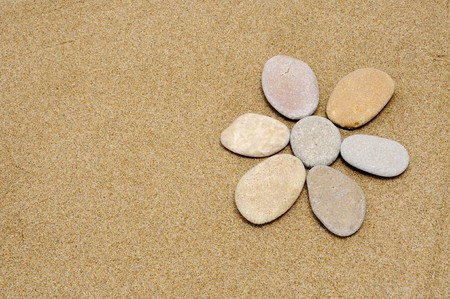 flower made with stones on a sand background Stock Photo - 6898285