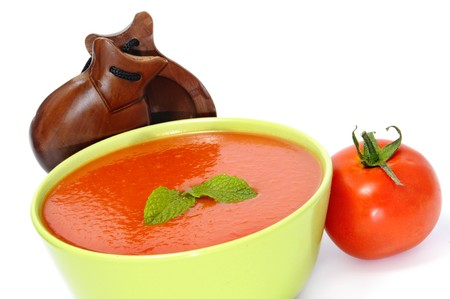 andalusian cuisine: a bowl with gazpacho and castanets isolated on a white background