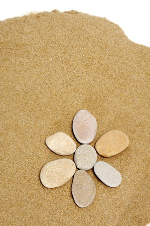 inukshuk: flower made with stones on a sand background Stock Photo