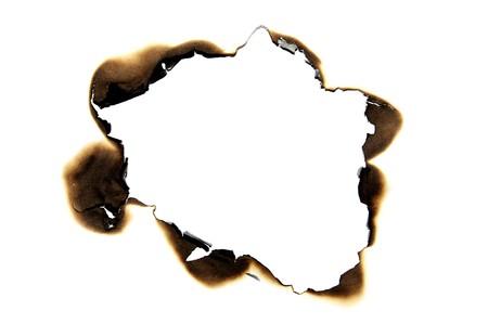 papel quemado: agujero quemado sobre un fondo de white paper