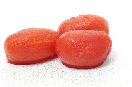 some whole peeled tomatoes isolated on a white background