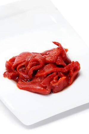 asados: un plato de picado los pimientos rojos aislado en un fondo blanco