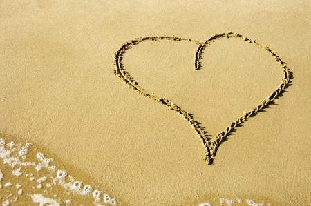evoking: a heart drawn on the sand of the beach Stock Photo
