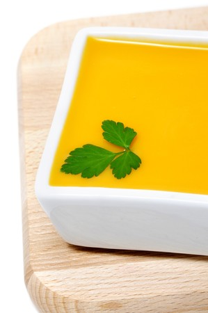 a bowl of pumpkin soup isolated on a white background photo