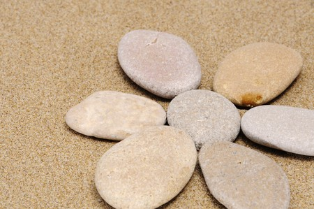 flower made with stones on a sand background photo
