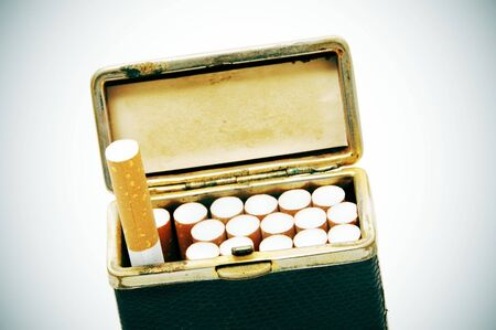 degraded: old cigarette case with cigarettes on a degraded background