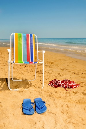 nudism: deckchair, swim suit and flip-flops on the beach Stock Photo