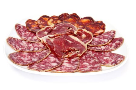 peppered: a plate with spanish chorizo, salami and jamon serrano on a white background Stock Photo