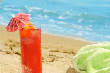 a cocktail and a towel on the sand of a beach Stock Photo - 7306338