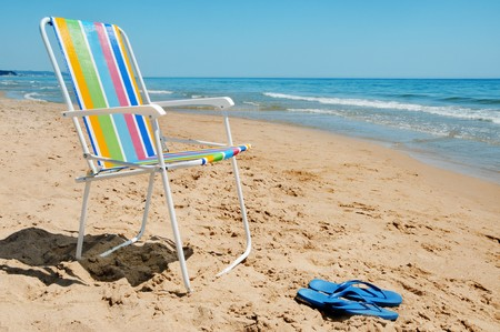 a deckchair and a pair of flip-flops on the beach photo