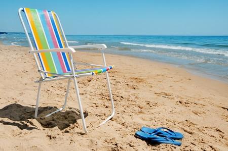 una tumbona y un par de sandalias en la playa  Foto de archivo