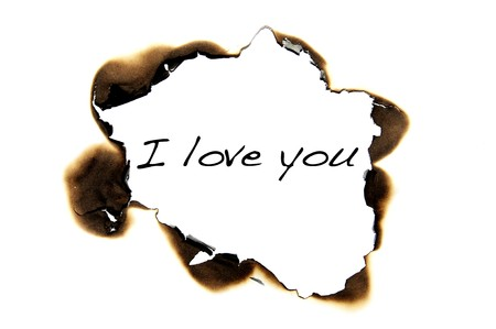 I love you written on a burned hole on a white paper background photo