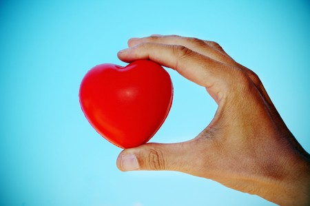 a hand holding a red heart in a vignetted background photo
