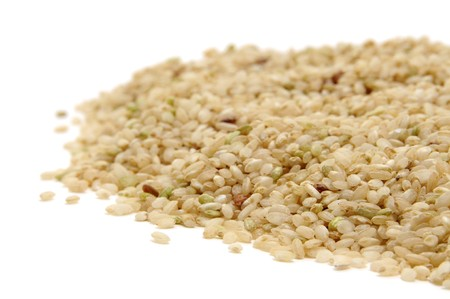 closeup of a pile of brown rice isolated on a white background photo