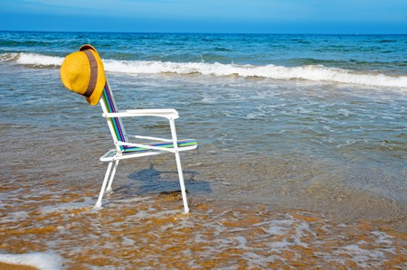 a colored deckchair and a straw hat on the beach Stock Photo - 7435731