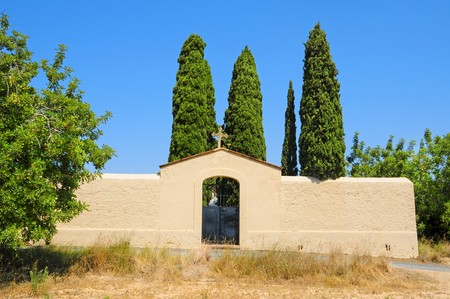 facade with a cross in an old cemetery in Spain photo